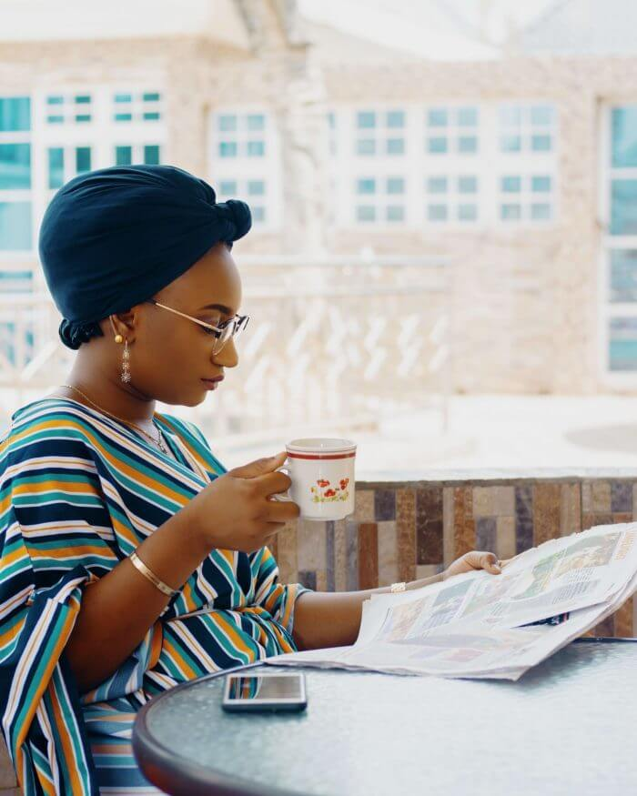 African lady reading a paper and sipping a drink, ectopic pregnancy can happen in a woman of child bearing age.