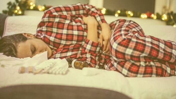 Lady of afrocarribbean origin in red stripped pajamas lying on a bed in obvious pain - possibly from a stomach ulcer