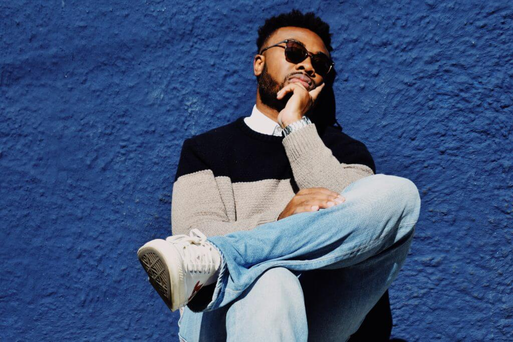 I snore - but why? Young man of African origin in sunglasses, jumper and jeans with his knee on the other leg.