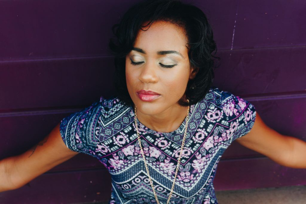 Photo of a lady of african background with eyes closed in a serene pose wearing a geometric pattern blouse.