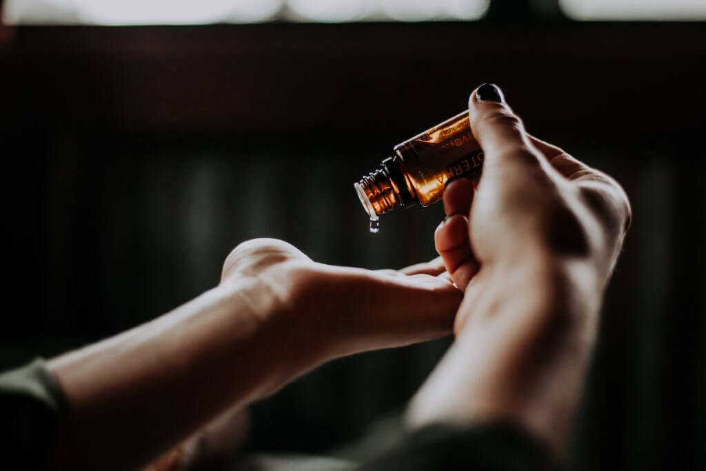 A pair of healing hands of a Natural Therapy Practitioner applying healing oil from a brown bottle.