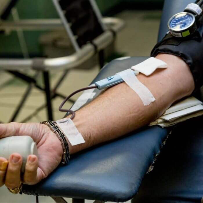 Man with arm outstretched during blood transfusion