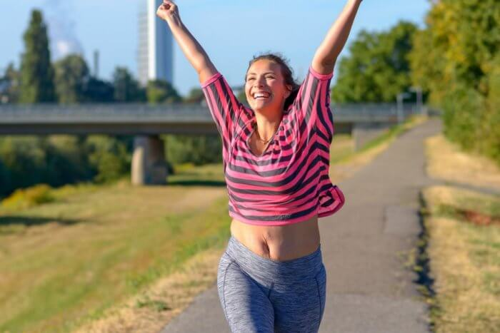 Lady in work out clothinglooking happy and raising arms following a run - The after exercise buzz can last longeer if you take some conscious steps