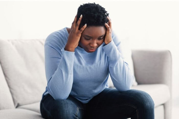 Worried looking lady of african origin sitting on sofa dressed in jeans and light blue blouse. - image depicts brain fog from long covid