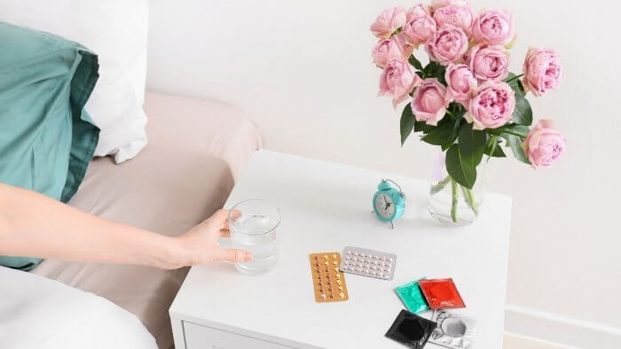 Best Non Hormonal Birth Control Option image of lady's hand reaching for a glass of water with some pills and condoms on the top
