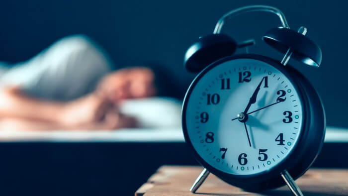 Alarm clock in the foreground with blurry photo of man asleep on bed behind
