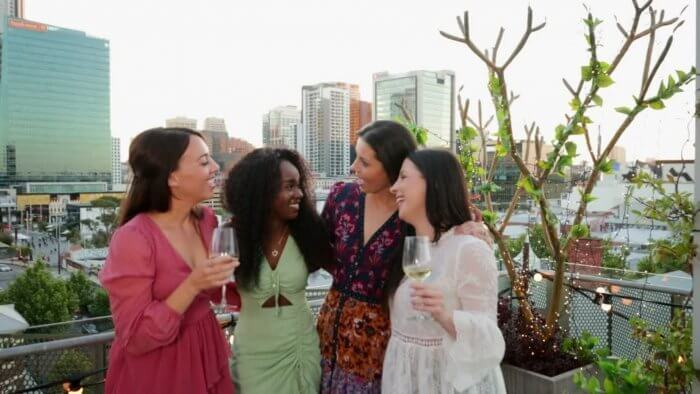 heart healthy diet - group of ladies in evening wear chatting and takng cocktail drinks
